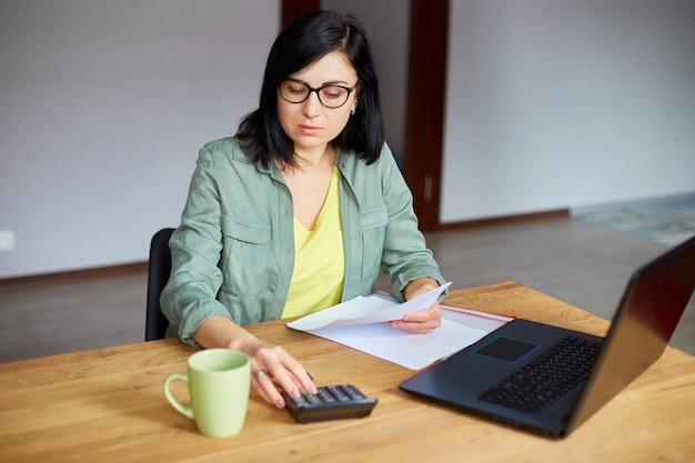 Mulher contadora sentada calculando despesas na calculadora na mesa de madeira, local de trabalho moderno
