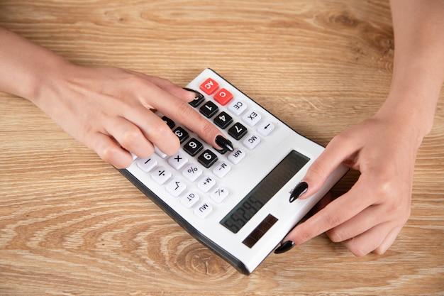 Mulher contando com uma calculadora