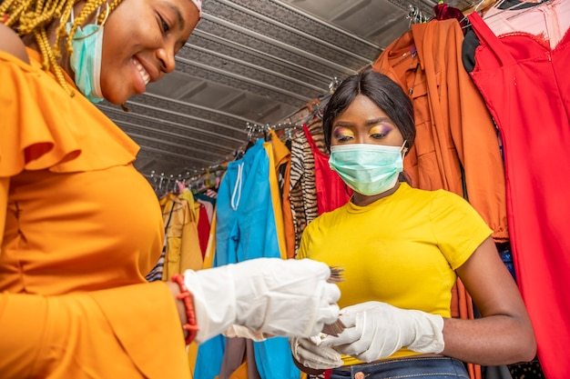 Mulher contando dinheiro em uma boutique local, usando máscara facial para se proteger contra o coronavírus covid-19