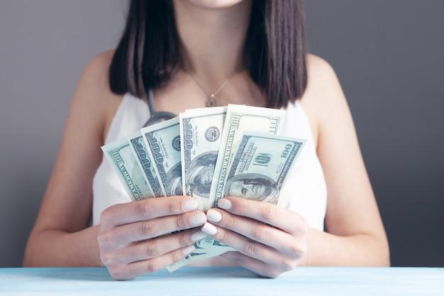Mulher contando dinheiro na frente da mesa