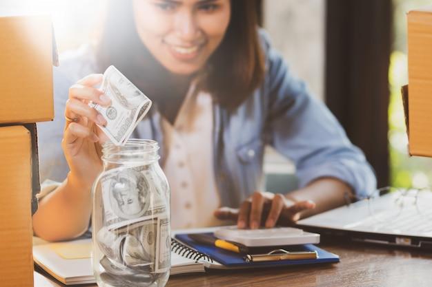 Mulher contando e colocando notas de dinheiro para a garrafa de vidro para poupar dinheiro.