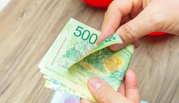 Mulher contando notas de dinheiro argentinas