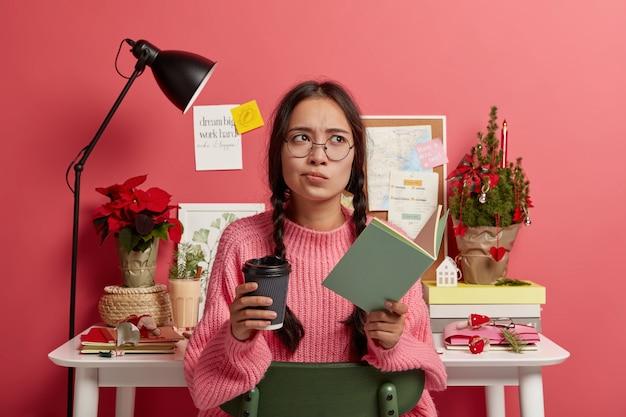 Mulher contemplativa séria usa óculos e macacão grande, segura um copo de papel com café, livro didático para educação