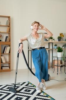 Mulher contemporânea alegre, usando fones de ouvido e roupas de casa, curtindo sua música favorita e limpando o chão da sala com aspirador de pó