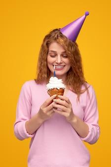 Mulher contente com um chapéu de festa fazendo um desejo com um bolinho de aniversário