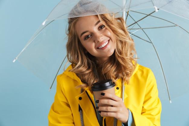 Mulher contente de 20 anos com capa de chuva amarela sob um guarda-chuva transparente com café para viagem