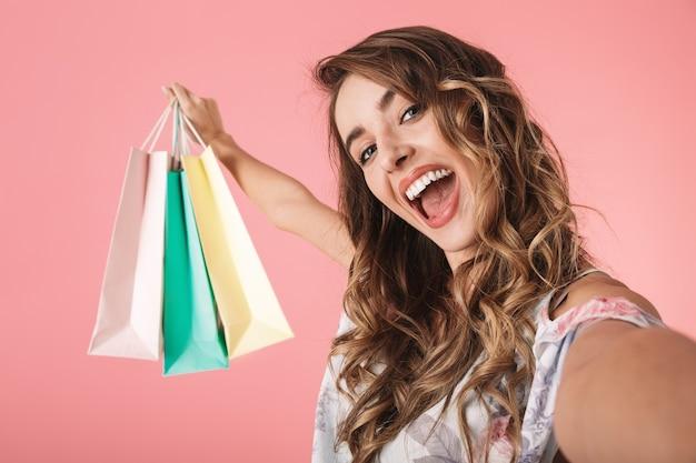 Mulher contente em vestido segurando sacolas de compras coloridas e tirando uma selfie, isolada em rosa