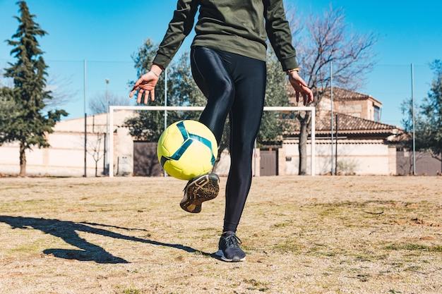 Mulher controlando e chutando a bola com os pés. campo de futebol de campo. conceito de futebol feminino.