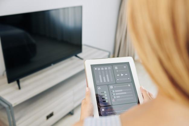 Mulher controlando tv com aplicativo móvel