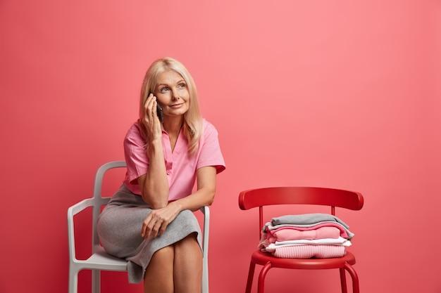 Mulher conversa ao telefone discute algo tem expressão sonhadora posa em uma cadeira confortável passa o tempo livre em casa isolada no rosa