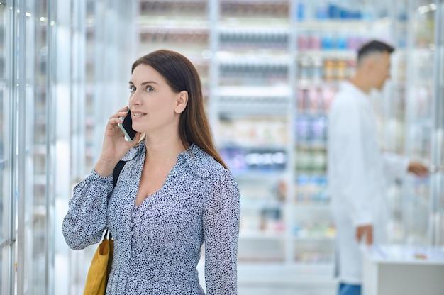 Mulher conversando ao telefone em uma drogaria