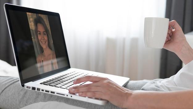 Mulher conversando com um amigo na chamada de vídeo e bebendo café