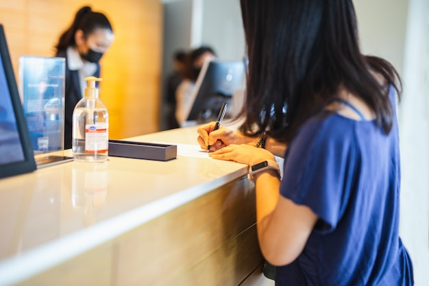 Mulher convidado assinar a conta na recepção do hotel.