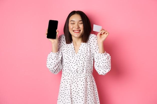 Mulher coreana alegre mostrando a tela do smartphone e o cartão de crédito, pagando um pedido pela internet