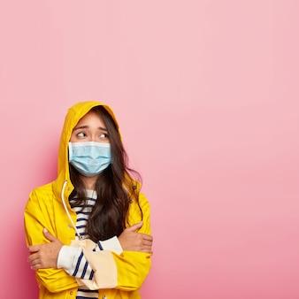 Mulher coreana triste e preocupada que pegou um resfriado após passear durante um clima frio e chuvoso, mantém as mãos cruzadas