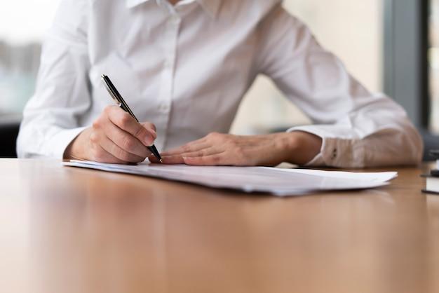 Mulher corporativa, escrevendo no papel