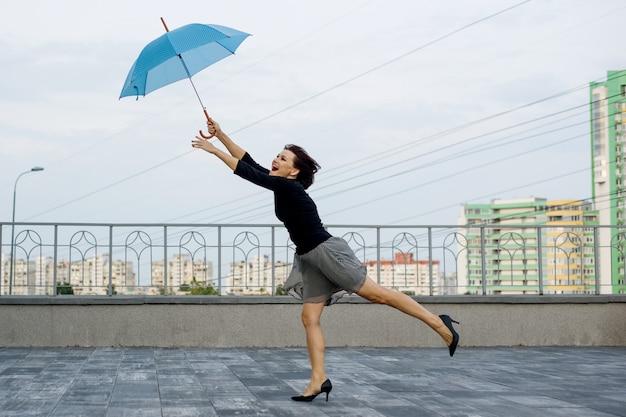 Mulher corre atrás de um guarda-chuva contra o pano de fundo da cidade