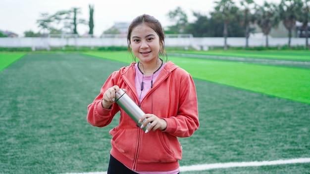 Mulher corredor asiática bebendo água no estádio