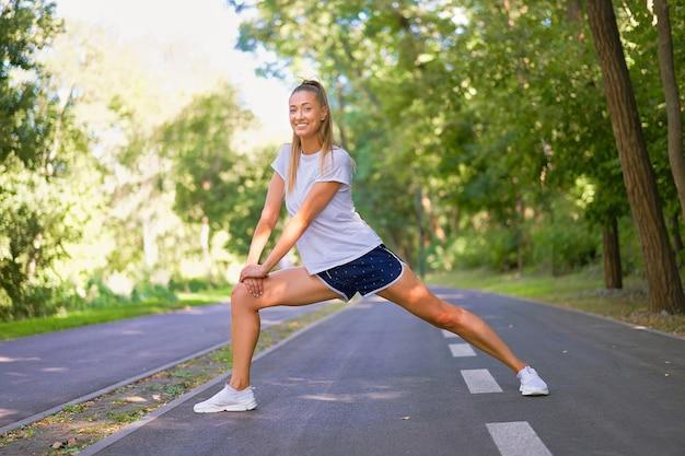 Mulher corredora esticando as pernas antes de correr no parque de verão. mulher de meia-idade, atlética, aquecendo o corpo antes de correr