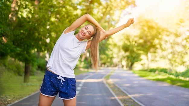 Mulher corredora esticando os braços antes de correr no parque de verão. mulher de meia-idade, atlética, aquecendo o corpo antes de correr