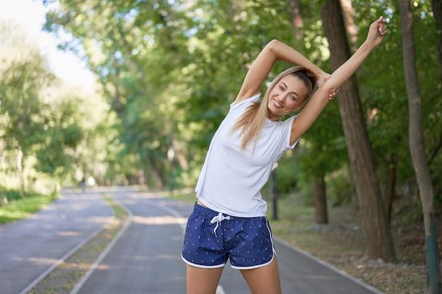 Mulher corredora esticando os braços antes de se exercitar na manhã