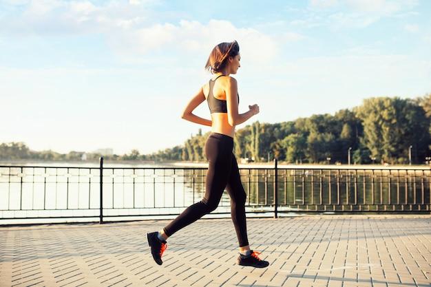 Mulher correndo à beira do lago ao pôr do sol