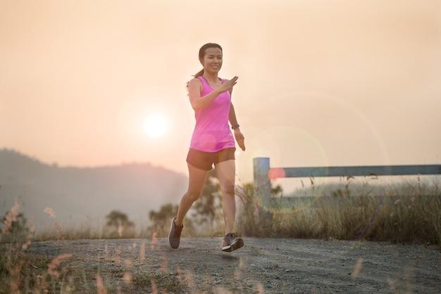 Mulher correndo ao ar livre em uma noite linda de verão ensolarado