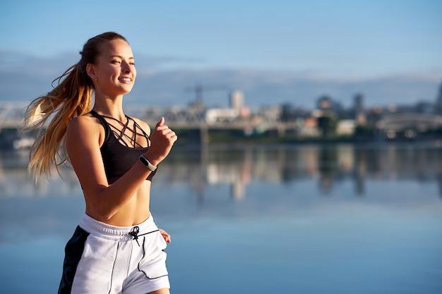 Mulher correndo ao nascer do sol. manhã, movimentando-se na praia ou na costa do rio no fundo da cidade urbana