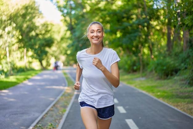 Mulher correndo asfalto parque de verão. ativo desportivo caucasiano feminino exercício matinal