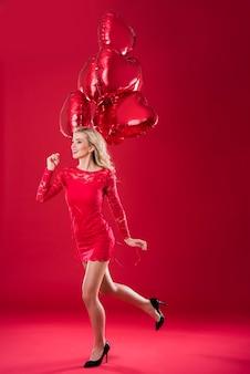 Mulher correndo com balões vermelhos em formato de coração