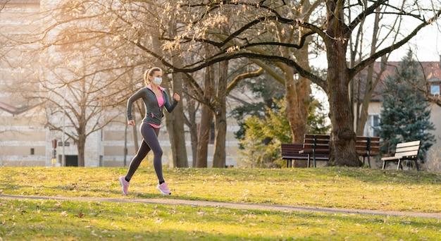 Mulher correndo com máscara facial para se manter saudável durante covid-19