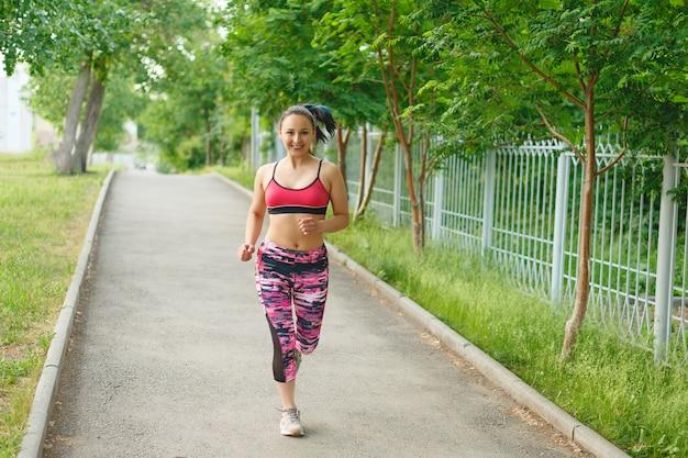 Mulher correndo. corredor feminino, movimentando-se durante o treino ao ar livre em um parque. lindo apto garota. modelo de fitness ao ar livre.