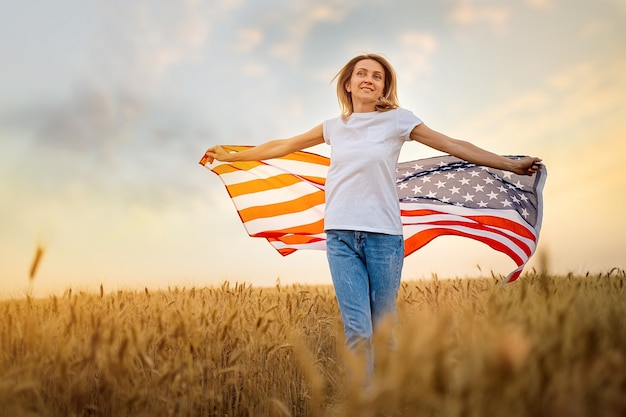 Mulher correndo e pulando despreocupada com os braços abertos sobre o campo de trigo, segurando a bandeira do eua.