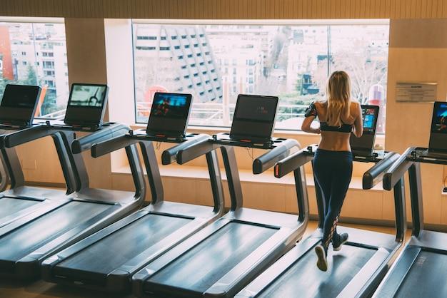 Mulher correndo em esteiras em uma academia com bela luz das máquinas de ginástica de janela