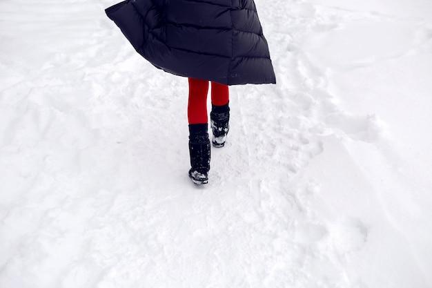 Mulher correndo em um campo nevado com uma jaqueta e óculos escuros