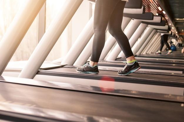 Mulher correndo em uma academia em uma esteira para exercícios, exercícios físicos e estilo de vida saudável