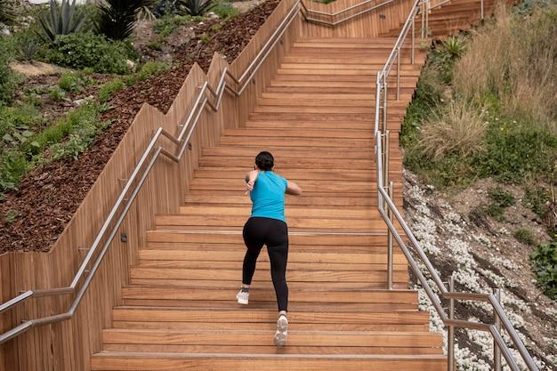 Mulher correndo em uma camisa azul e subindo uma escada de madeira