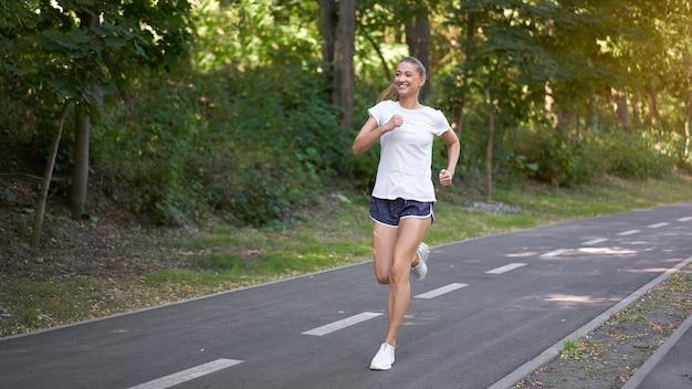 Mulher correndo em uma estrada de asfalto em um parque de verão
