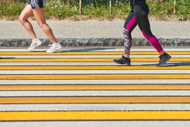 Mulher correndo na faixa de pedestres, copie o espaço. atlética mulher correndo em roupas esportivas na estrada da cidade. estilo de vida saudável, esporte fitness hobby