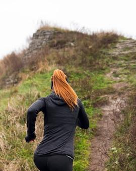 Mulher correndo na natureza por trás de tiro