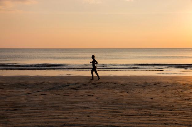 Mulher correndo na praia ao pôr do sol, estilo de vida saudável