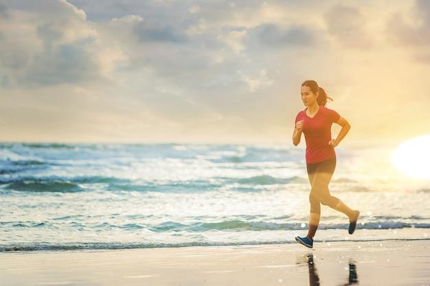 Mulher correndo na praia com o por do sol.