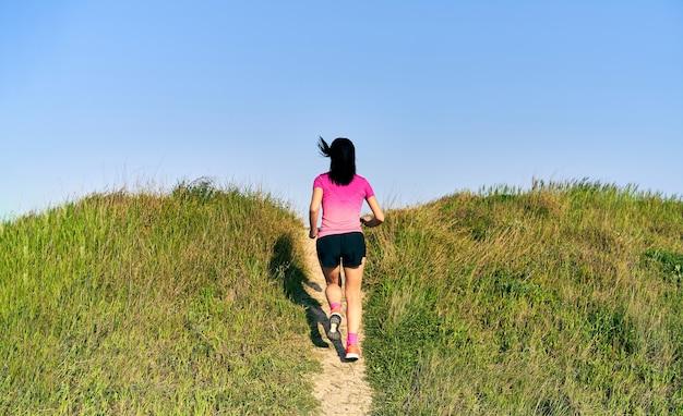 Mulher correndo para o topo da pista em um caminho reto e alongado em um campo gramado.