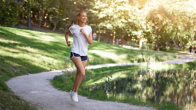 Mulher correndo parque de verão na estrada