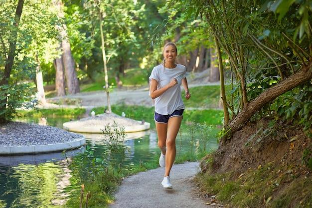 Mulher correndo parque de verão perto do lago ativo desportivo caucasiano feminino treino matinal