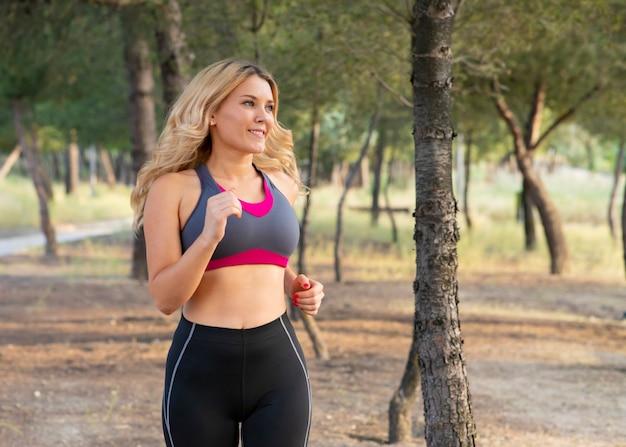 Mulher correndo pela floresta feliz. conceito de esporte ao ar livre
