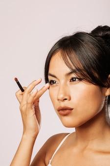 Mulher corrigindo sua maquiagem