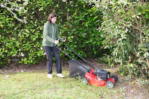 Mulher corta a grama entre as árvores em seu jardim