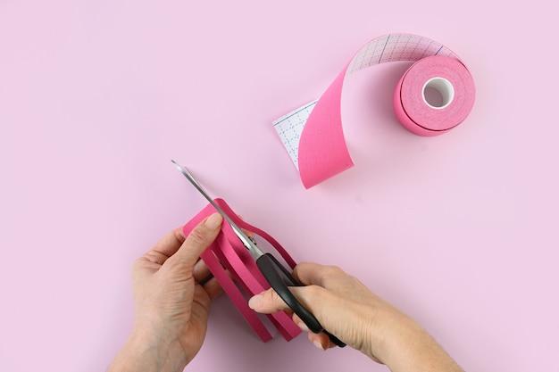Mulher corta as fitas rosa em forma de polvo para corrigir o corpo e eliminar a celulite. correção corporal e aceleração do fluxo de linfa.