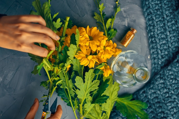 Mulher corta as flores de crisântemo amarelo para um vaso em uma mesa de loft antigo